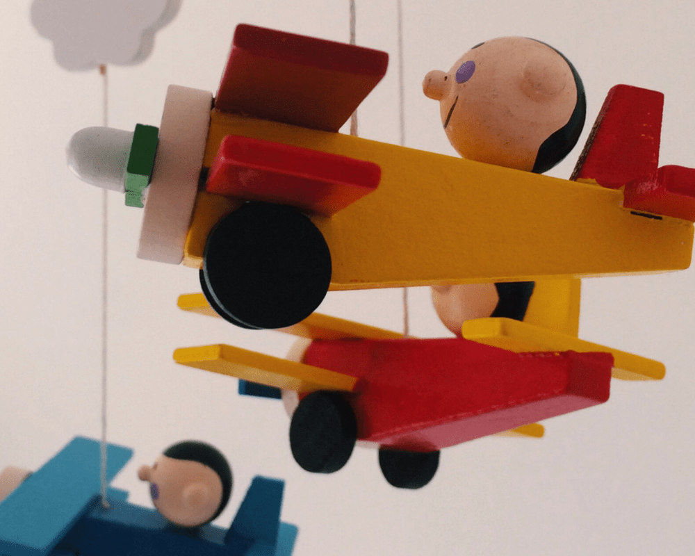 A close-up photograph of a brightly coloured wooden mobile of some very cute aeroplanes and clouds _ Little Mister H's rainbow themed nursery - a tour and vlog - Mrs H's favourite things