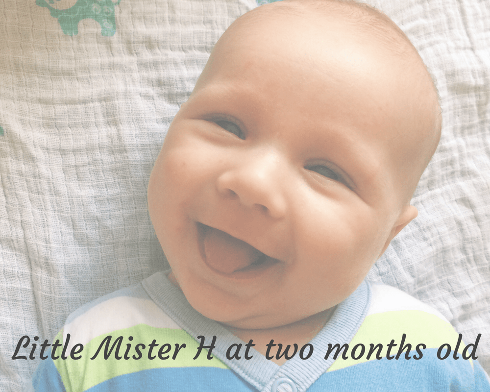 "A faded photograph of a smiling baby boy who is wearing a light green, light blue and white striped babygrow and is lying on a white and blue patterned muslin - includes the title of the blog post ""Little Mister H at two months old"" - Mrs H's favourite things"