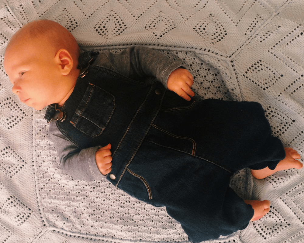 A photograph of a little boy lying diagonally on a blue crotched blanket - he is looking to his right and is wearing a pair of denim dungarees and a blue and white striped bodysuit - Little Mister H at two months old - Mrs H's favourite things