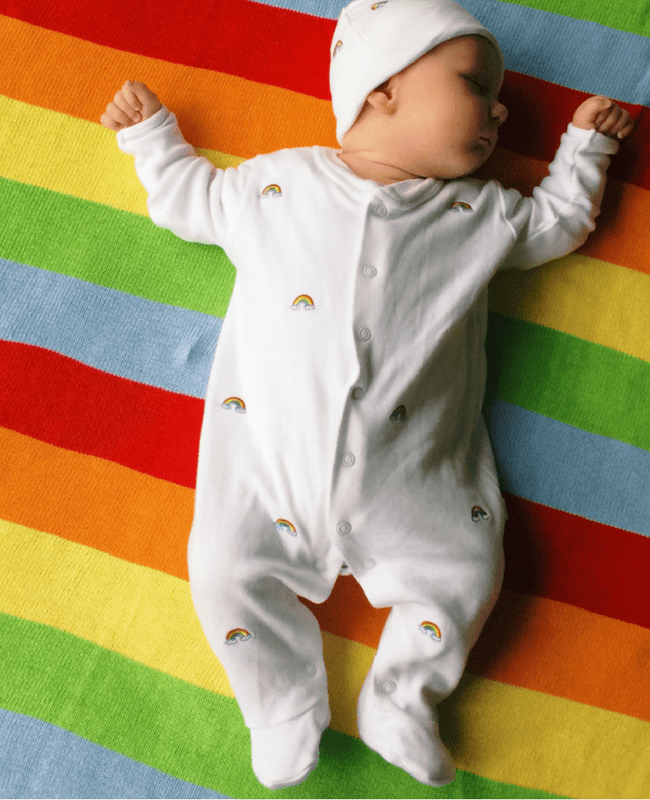 My rainbow baby_5_Mrs H's favourite thingsA gorgeous baby boy asleep on a brightly coloured rainbow blanket - he is wearing a Jojo Maman Bebe sleepsuit and matching hat - they are white and covered in tiny embroidered rainbows - My rainbow baby - Mrs H's favourite things
