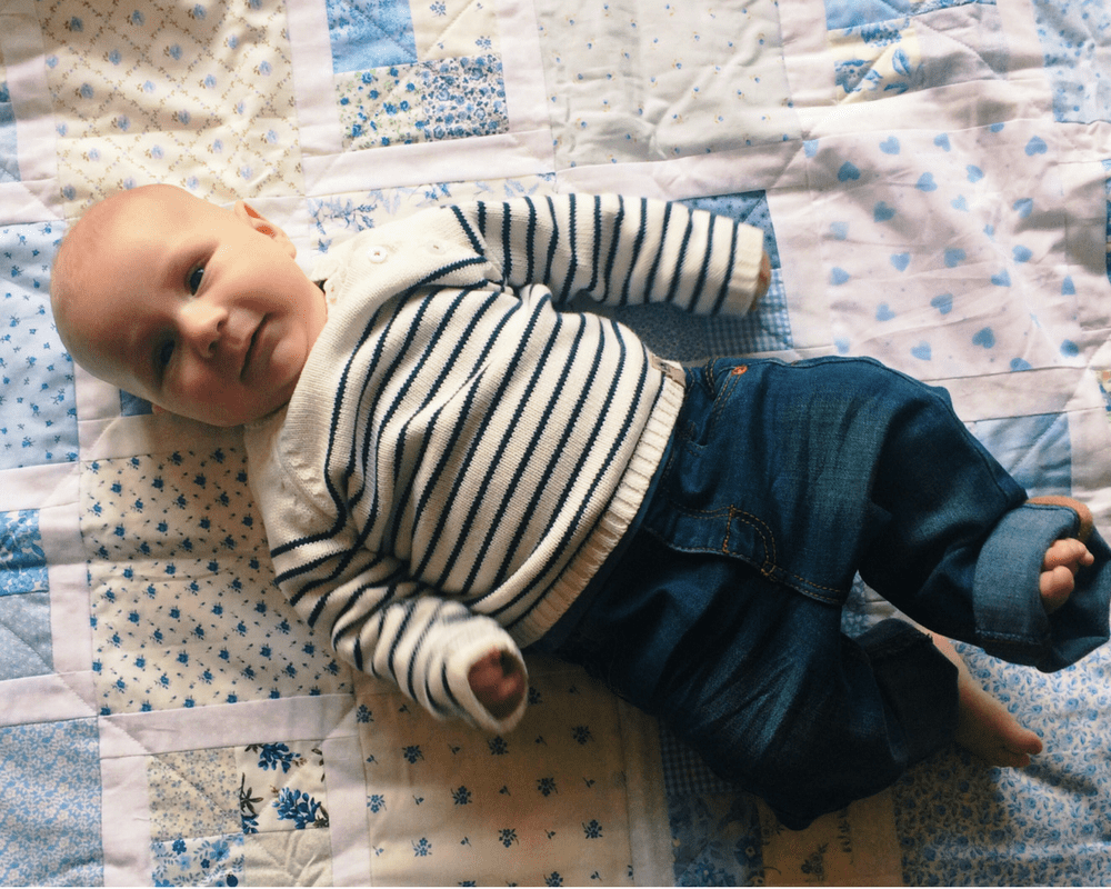 A photograph of a three month old boy wearing a pair of jeans and a cream and navy Breton jumper - The perfect capsule wardrobe for kids from Vertbaudet_Mrs H's favourite things
