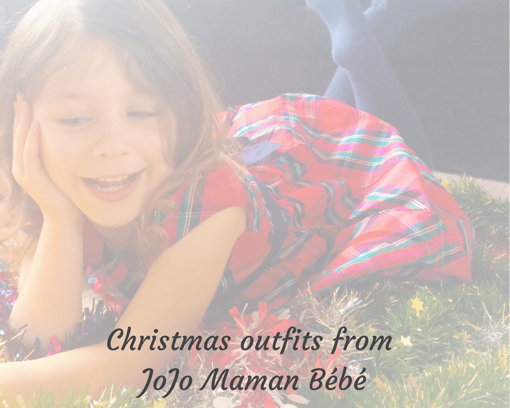 """A faded photograph of a little girl wearing a red tartan party dress from JoJo Maman Bébé and lying on her tummy in some tinsel and includes the text """"Christmas outfits from JoJo Maman Bébé"""" - Mrs H's favourite things"""