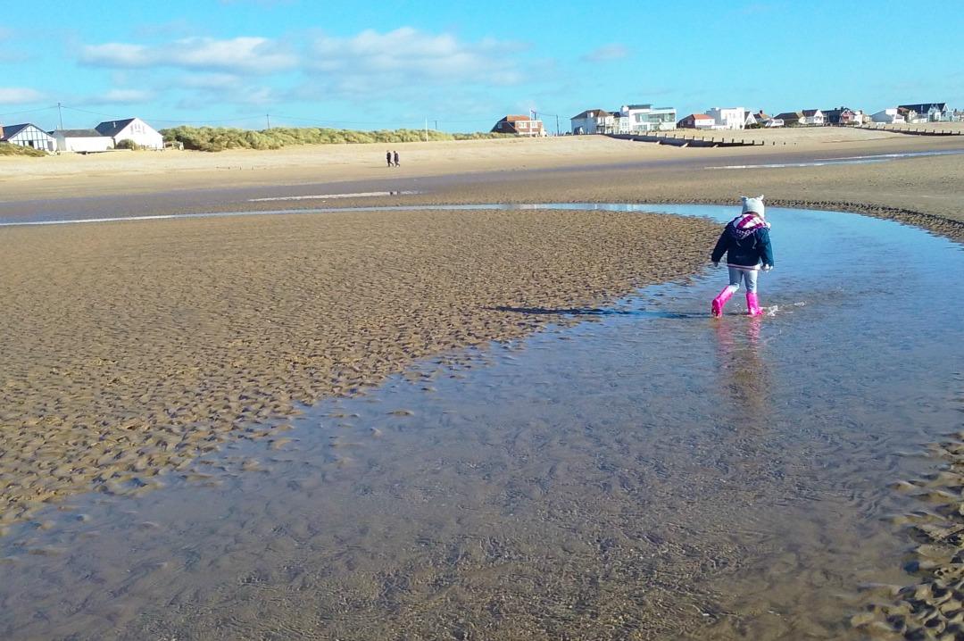 A coloured photograph of a little girl dressed in cold weather gear walking across Camber Sands beach on a sunny winter's day with the beach houses and a bright blue sky in the background - The (not big of fat) quiz of the year _ Mrs H's favourite things