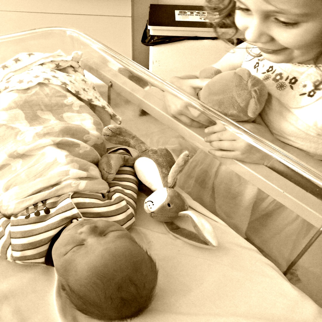 A sepia photograph of a gorgeous little girl looking adoringly at her hew born brother as he lies in the cot - The (not big or fat) quiz of the year - Mrs H's favourite things