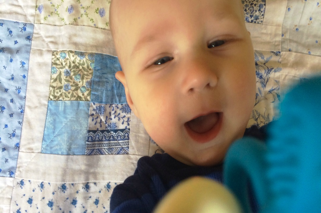 A photograph of a six month old baby boy lying on a pale blue patchwork blanket and waving the teething toy Matchstick Monkey - My top 5 teething products _ Mrs H's favourite things