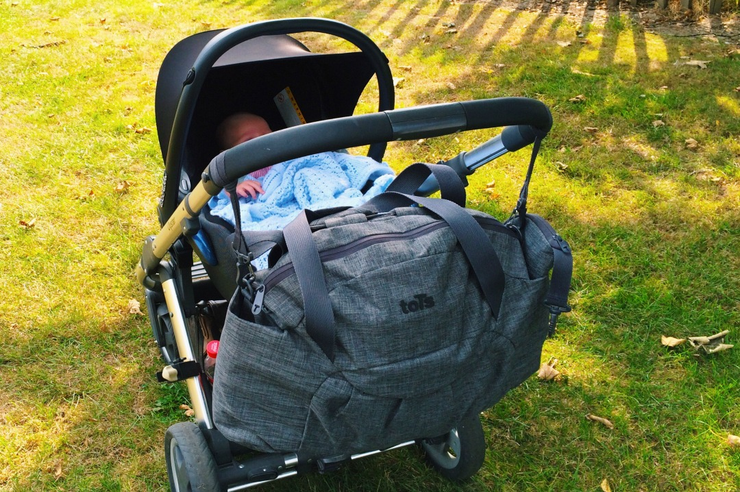 A photograph of the toTs by SmarTrike Dark Grey Melange Voyage Changing Bag hanging on a baby pram outside on some grass in the sun toTs by SmarTrike Dark Grey Melange Voyage Changing Bag _ A review _ Mrs H's favourite things