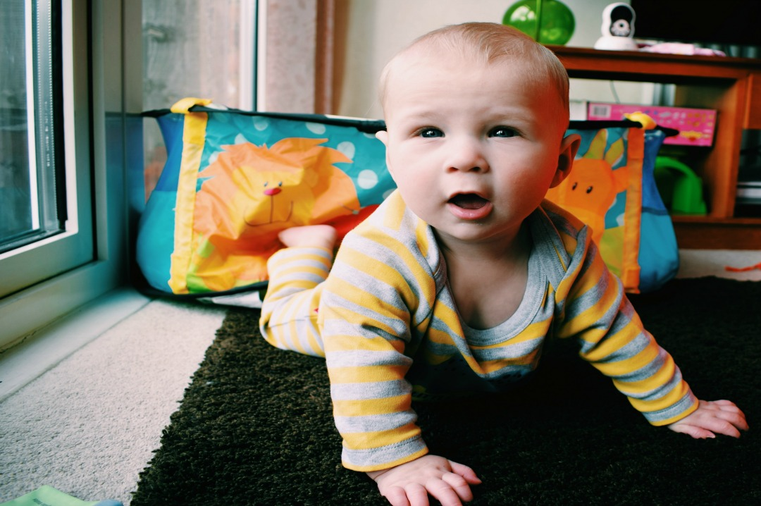 A photograph of our eight month old baby boy wearing a grey and yellow striped personalised dinosaur babygrow from Sgt. Smith, lying on his stomach and fully lifting his head, shoulders and chest off the ground - Little Mister H at eight months old - an update - Mrs H's favourite things