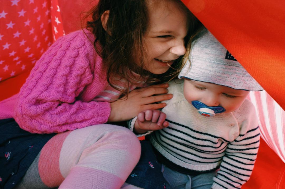A photograph of two children, a little girl and her baby brother, sitting inside a tee pee, playing and laughing and smiling together - To my children on mothers day - Mrs H's favourite things