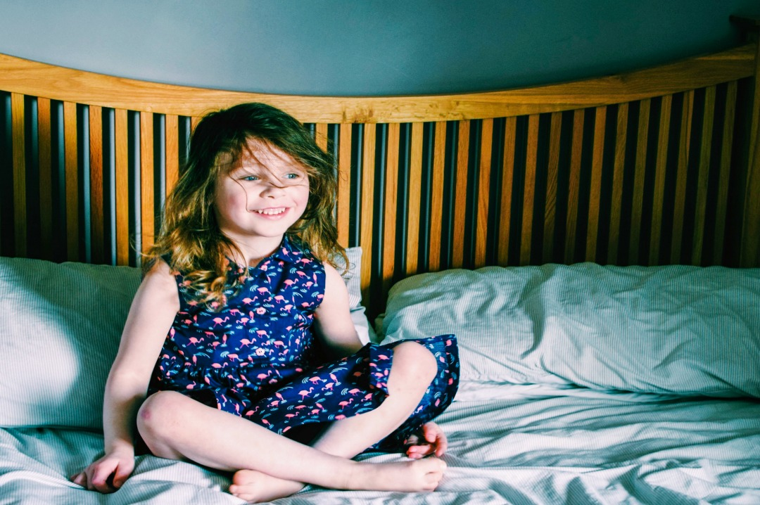 A photograph of a gorgeous three year old girl modelling some Beautiful Summer Clothes from JoJo Maman Bébé and particularly the Girls' Flamingo Shirt Dress - Beautiful Summer Clothes from JoJo Maman Bébé - Mrs H's favourite things
