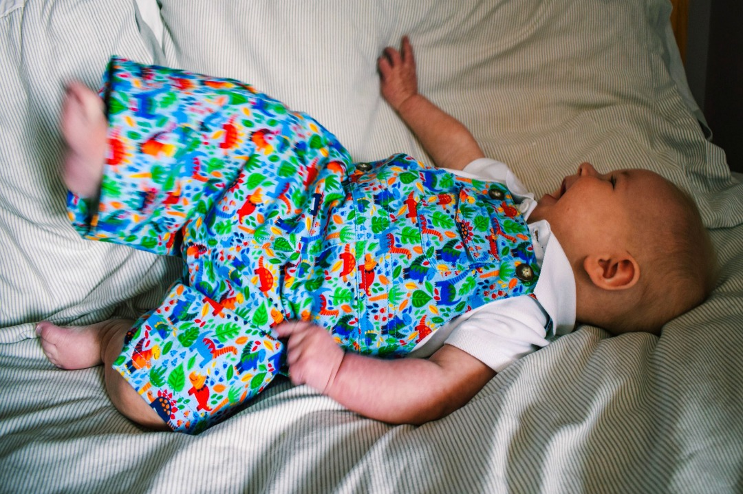 A photograph of a beautiful nine month old baby boy modelling some Beautiful Summer Clothes from JoJo Maman Bébé and particularly the Dinosaur Print Baby Dungarees and the White Poloshirt Baby Bodysuit - Beautiful Summer Clothes from JoJo Maman Bébé - Mrs H's favourite things