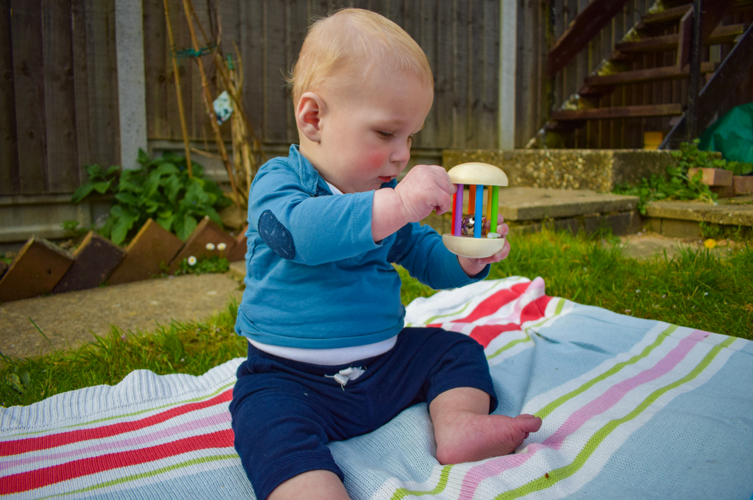 A photograph of a baby boy sitting on a striped blanket in a garden and playing with the Bigjigs Rainbow Rattle - Bigjigs Play Patrol Rainbow Rattle and Garden Bead Box - Mrs H's favourite things