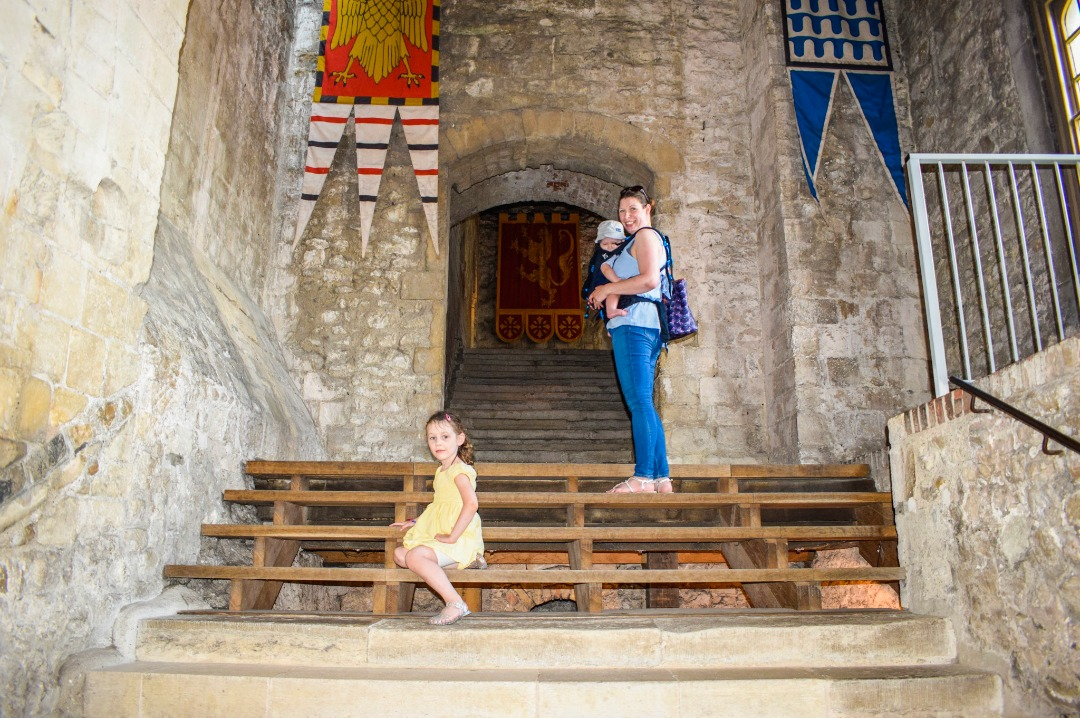 A photograph of a mother carrying her son in a baby carrier and with her daughter sitting near her while she stands on some steps at the entrance to the Great Tower at Dover Castle - A Day at Dover Castle with the Quinny Zapp Flex Plus - Mrs H's favourite things