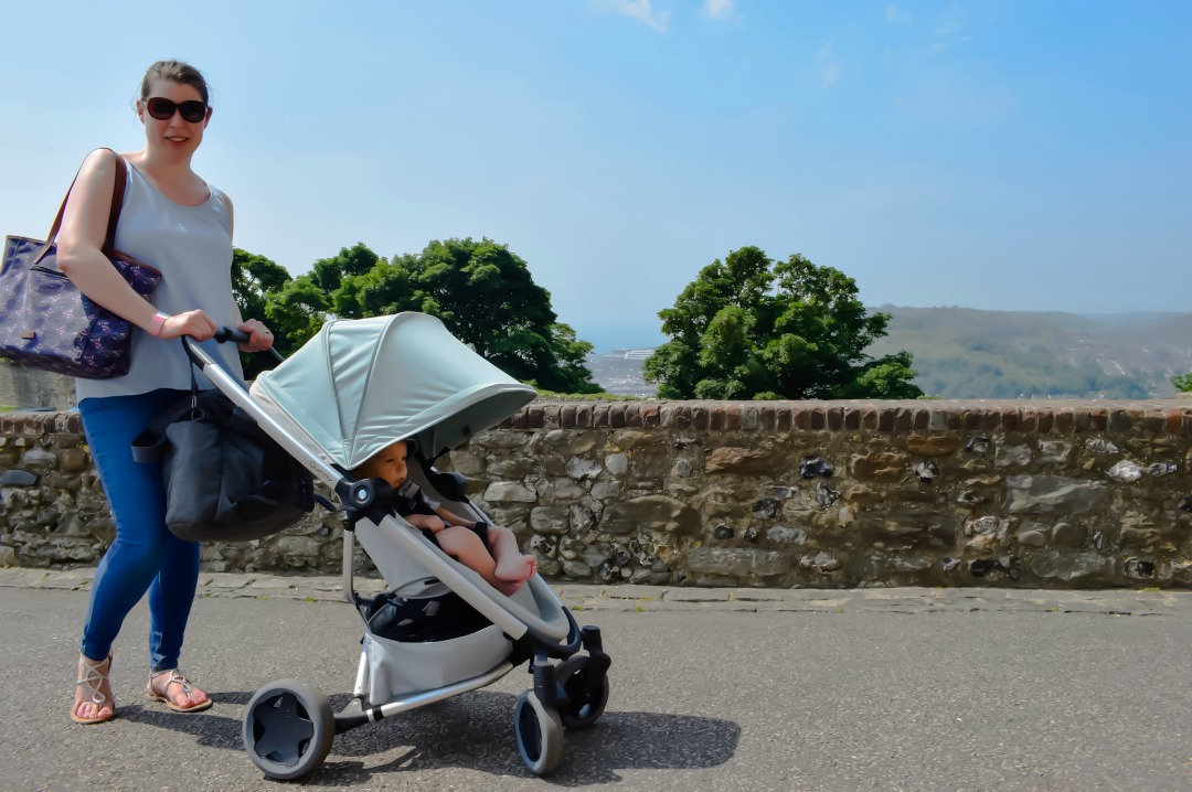 A photograph of a mother standing in front of a wall in Dover Castle in Kent, her baby sits in front of her in the Quinny Zapp Flex Plus in Frost on Grey - A Day Out at Dover Castle with the Quinny Zapp Flex Plus - Mrs H's favourite things
