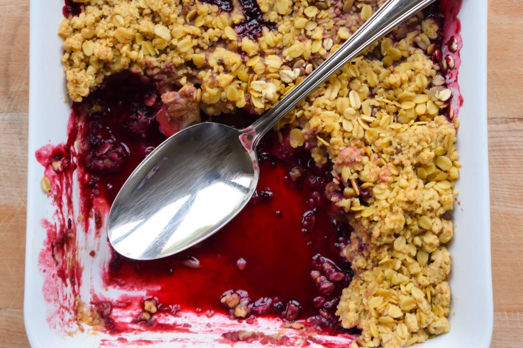 A photograph of the ultimate Apple and Blackberry Crumble in a white china dish on a wooden board and with a sterling silver serving spoon - the apple and blackberry crumble is filled with beautiful and succulent apple and blackberries and covered in a yummy crunchy crumble that is topped with porridge oats - The Ultimate Apple and Blackberry Crumble Recipe - Mrs H's favourite things