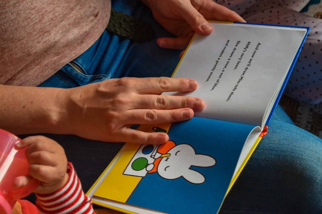 "A photograph of a mother and her two children settling down to a bedtime story of the Miffy book by Dick Bruna ""Miffy at School"" - the photograph shows a close up of one of the illustrations of Miffy in the book - Little Miss H in Miffy's World - Mrs H's favourite things"
