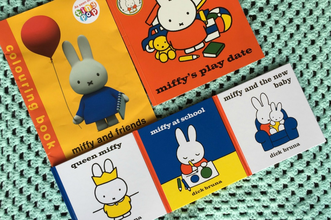 """A photograph of five Miffy books lying on a pale green baby blanket - the books are the larger """"Miffy and Friends colouring book"""", """"Miffy's Play Date Sticker Book"""", """"Queen Miffy"""", """"Miffy at School"""" and """"Miffy and the New Baby"""" - Little Miss H in Miffy's World - Mrs H's favourite things"""