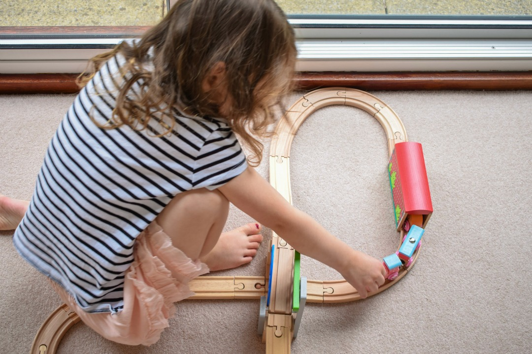 A photograph of a four year old girl sitting on the floor of her grandparent's living room playing happily with a train set and especially the Sweetland Express train from Bigjigs Railway part of Bigjigs Toys - Bigjigs Sweetland Express and Push-Along Rabbit - A Bigjigs Play Patrol Review - Mrs H's favourite things