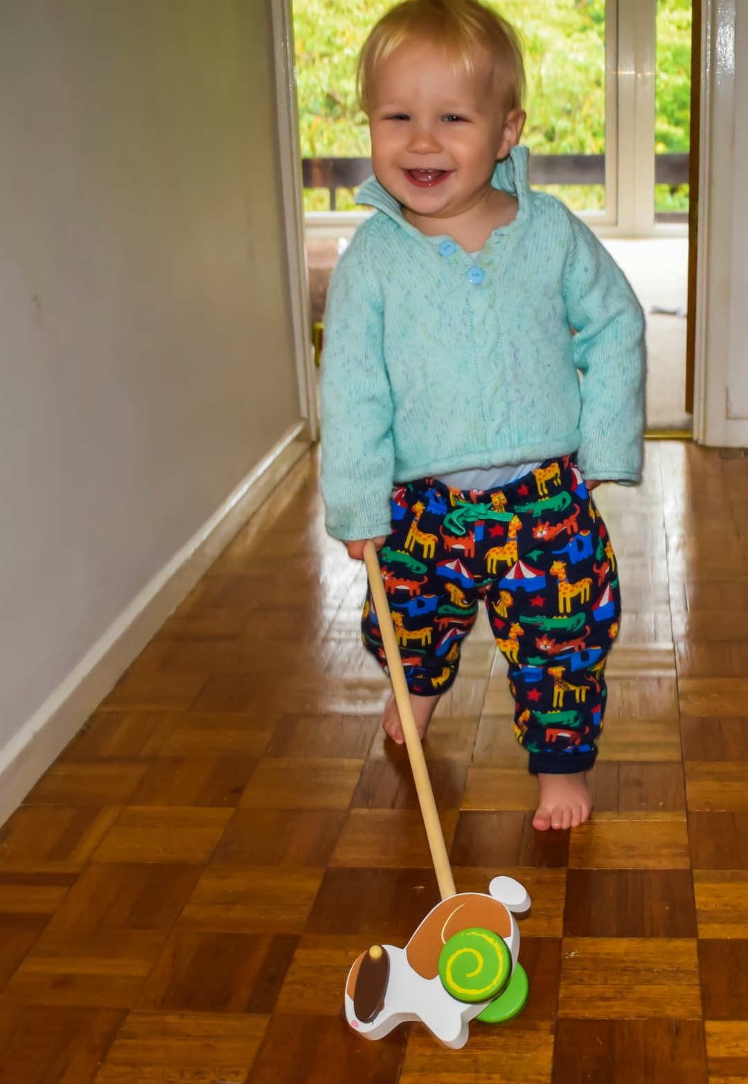 A 14 month old baby boy walking independently and pushing a Wooden Rabbit Push Along Toy from Bigjigs - he has a huge smile on his face and looks very happy - Bigjigs Sweetland Express and Push Along Rabbit - A Bigjigs Play Patrol Review - Mrs H's favourite things