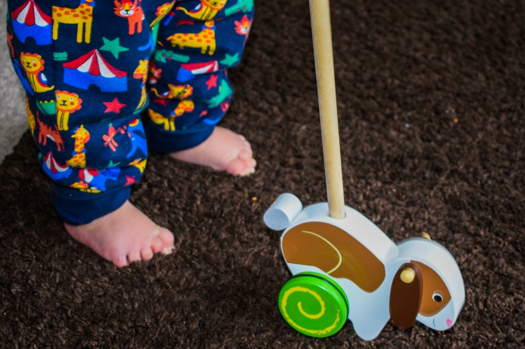 A photograph of the legs and tiny feet of a 14 month old baby boy standing independently and holding onto a Wooden Rabbit Push Along Toy from Bigjigs - Bigjigs Sweetland Express and Push Along Rabbit - A Bigjigs Play Patrol Review - Mrs H's favourite things