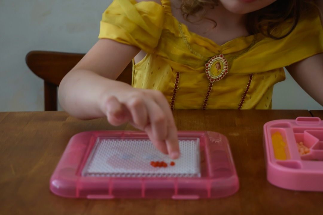 A photograph of a little girl (she is four years old) sitting at a dining room table wearing a Disney Princess Belle costume dress and playing with her Aquabeads Disney Princess Playset. She is creating the Disney Princess Ariel (The Little Mermaid) out of Aquabeads. Aquabeads Disney Princess Playset - a review of this brilliant quiet time activity for busy kids - Mrs H's favourite things