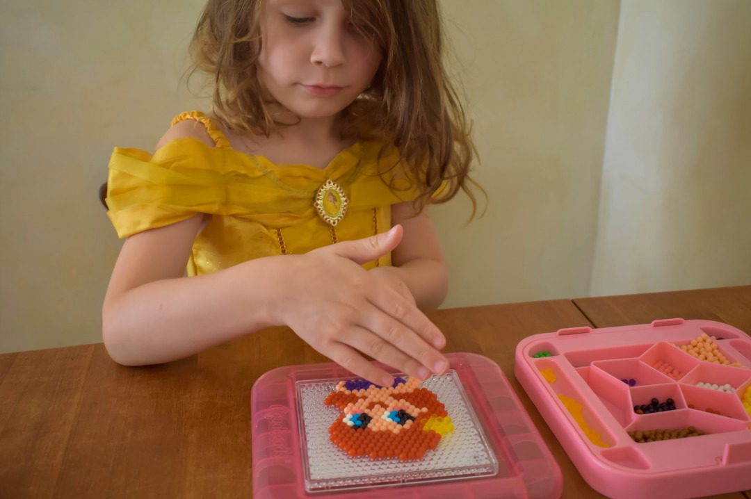A photograph of a little girl (she is four years old) sitting at a dining room table, wearing a Disney Princess Belle costume dress and making the Disney Princess Ariel with the Aquabeads Disney Princess Playset - Aquabeads Disney Princess Playset - A review of this brilliant quiet time activity for busy kids - Mrs H's favourite things