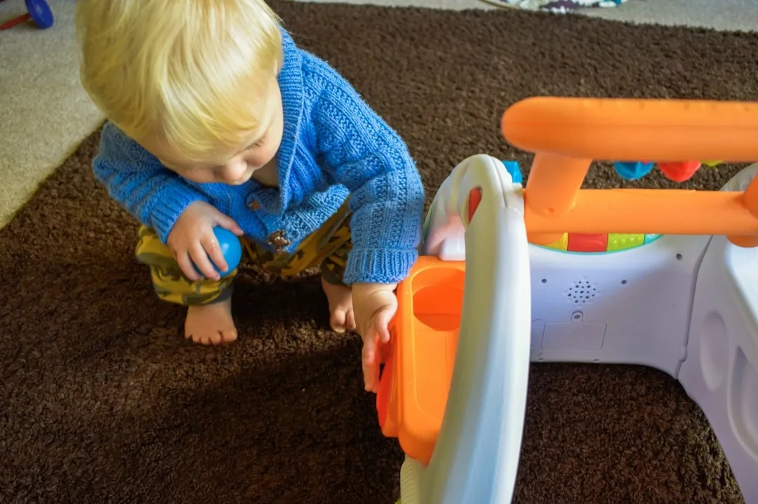 A photograph of a 14 month old baby boy playing with the mini ball run activity on the Infantino 3-in-1 Sensory Discovery Car Walker - First Steps with the Infantino 3-in-1 Walker - Mrs H's favourite things