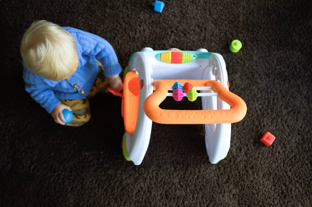A photograph of a 14 month old baby boy kneeling on a living room carpet and playing with the Infantino 3-in-1 Walker - he is playing with the mini ball run and loving exploring the different elements of the walker - First Steps with the Infantino 3-in-1 Walker - Mrs H's favourite things