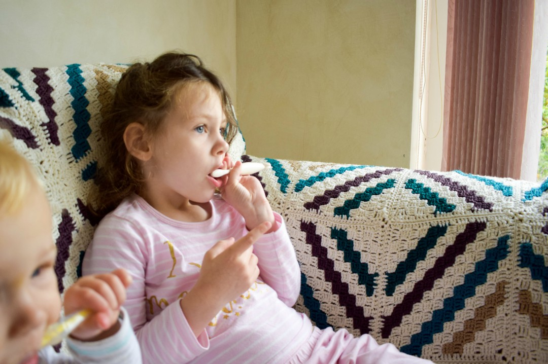 A photograph of a little boy and a little girl sitting on a sofa in their pyjamas and brushing their teeth with natural care toothbrushes and toothpastes - Natural Oral Care for the Whole Family with The Natural Family Company - Mrs H's favourite things