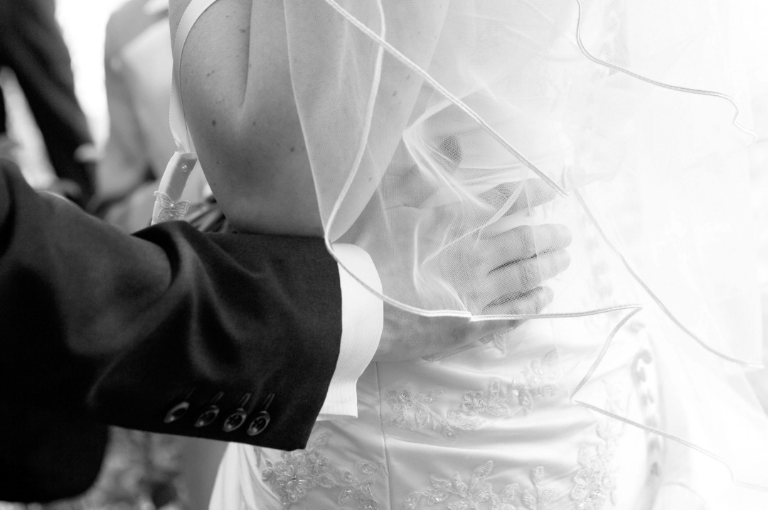 A black and white photograph from a wedding - the photo shows the groom's hand on the small of his new brides' dress - photo courtesy of Tara Lee Photography - Nine Reasons Why - Mrs H's favourite things