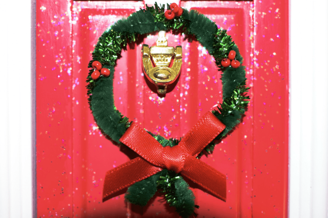 A photograph of the Opening Christmas Elf Door with Santa Claus Scene from Flitterbee - it is a beautiful miniature door painted in red and with glitter, a tiny Christmas wreath - Flitterbee Opening Christmas Elf Door - A Review - Mrs H's favourite things