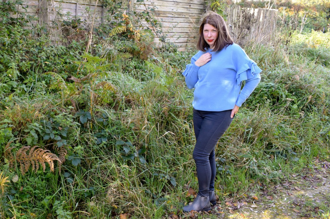 A photograph of a young brunette woman standing outside and wearing a blue ruffle sleeve jumper from JD Williams and grey skinny jeans and a pair of grey ankle boots - this is a photo of her modelling her new Mummy Style - Finding My Mummy Style With JD Williams and their Autumn/ Winter Collection - Mrs H's favourite things