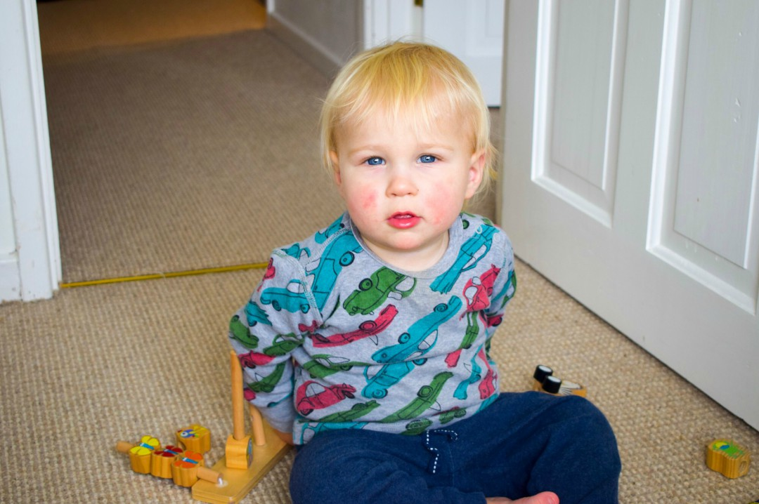 A photograph of a blonde haired, rosey cheeked and blue eyed 16 month old baby boy sitting on his bedroom floor and playing with some wooden toys - The Day I Closed The Door and Walked Away - Mrs H's favourite things