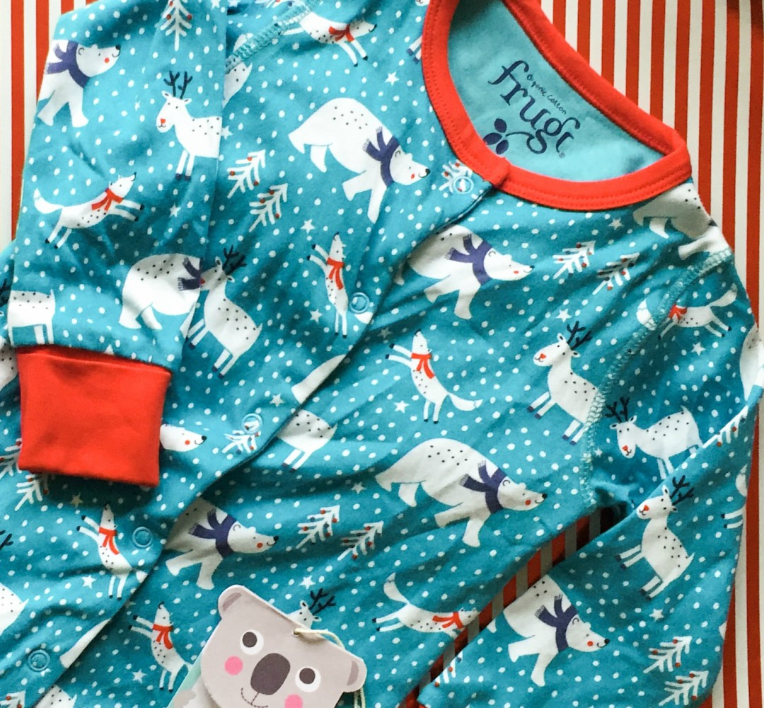 A photograph of a turquoise, blue, white and red Christmas babygrow from Frugi - it has the cutest arctic animals print - Our Christmas Eve box - What's inside? - Mrs H's favourite things