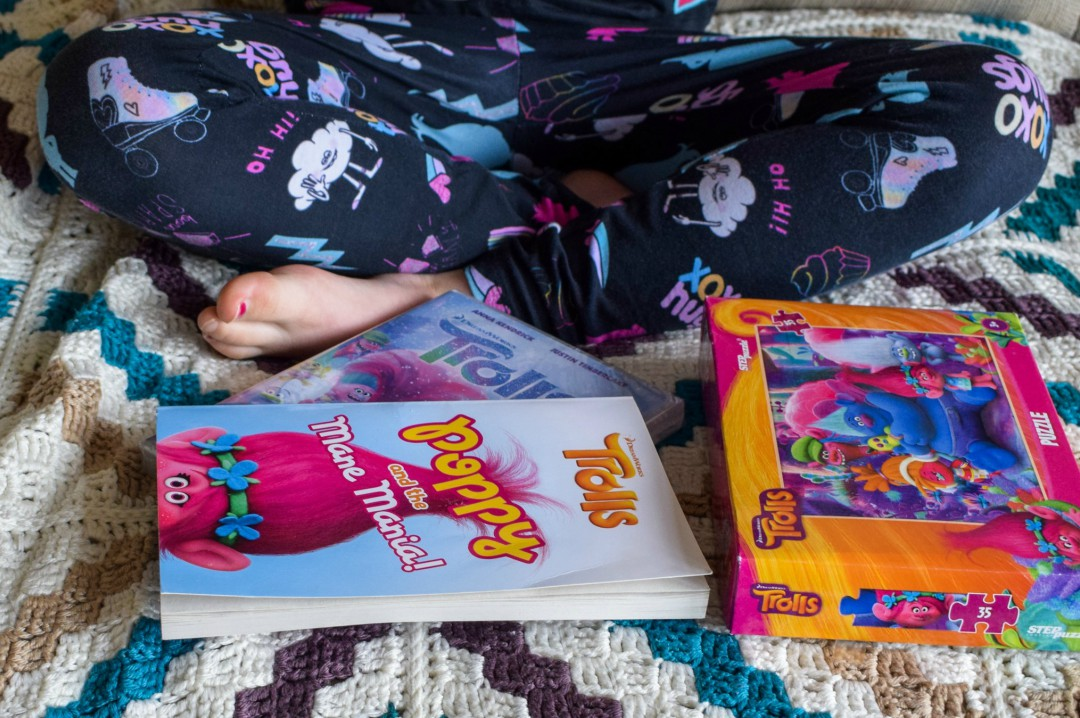 A photograph of a little girl sitting cross legged on a sofa - in front of her are a copy of a Trolls book, the Trolls Holiday DVD and a Trolls jigsaw - the little girl is also wearing Trolls merchandise - Having a Troll-tastic Christmas with Trolls Holiday - Mrs H's favourite things