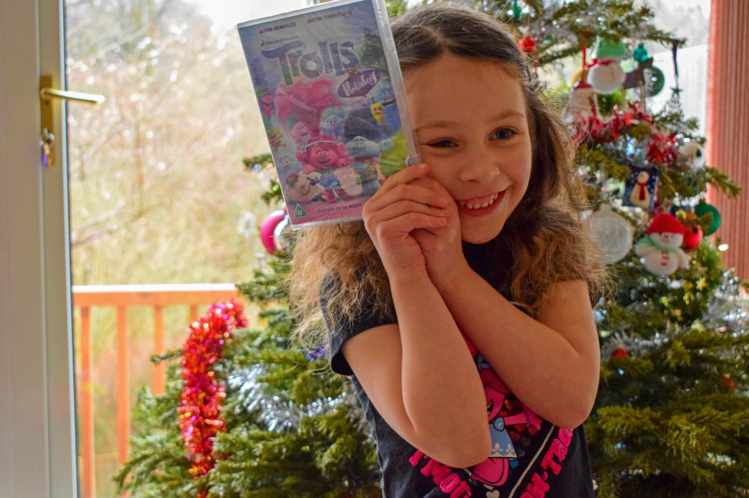 A photograph of a little girl standing in front of a Christmas tree. She is wearing a Trolls t-shirt from George in ASDA. She is also holding a copy of Trolls Holiday - Having a Troll-tastic Christmas with Trolls Holiday - Mrs H's favourite things