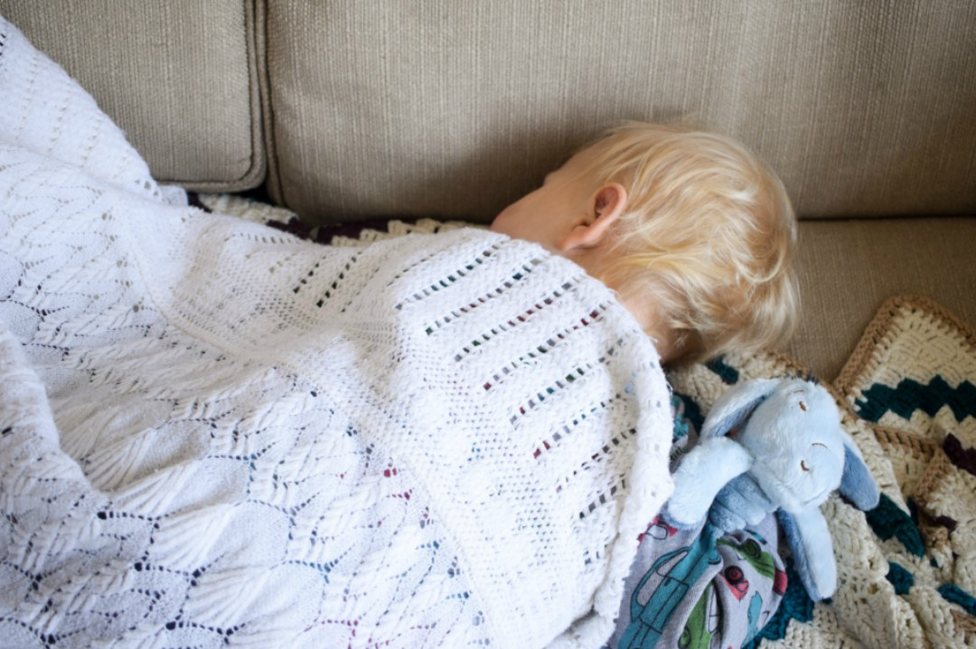 A photograph of a little boy of 16 months old sleeping on a sofa and covered in a cream baby blanket - tucked under his arm is the Eeyore Comfort Blanket part of the Classic Pooh Collection from Rainbow Designs Ltd. - Rainbow Design Ltd's Classic Winnie the Pooh toy collection - Eeyore Comfort Blanket and Tigger Soft Toy - A review and a giveaway - Mrs H's favourite things
