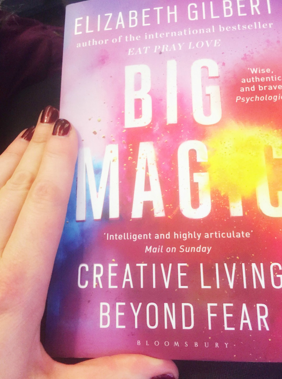 A photograph of a manicured hand holding a copy of Elizabeth Gilbert's book Big Magic - Our Weekend Happy #2 - Pampering, Pyjamas and Muddy Puddles - Mrs H's favourite things