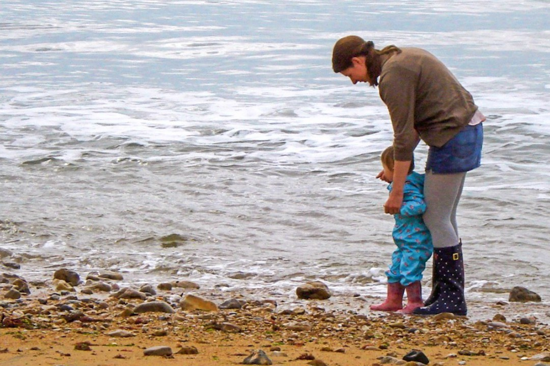 A photograph of a mother and her young daughter in wet weather gear paddling in the ocean - The Declaration of Motherhood - Mrs H's favourite things - a post about being a mother, about being equal and about supporting each other
