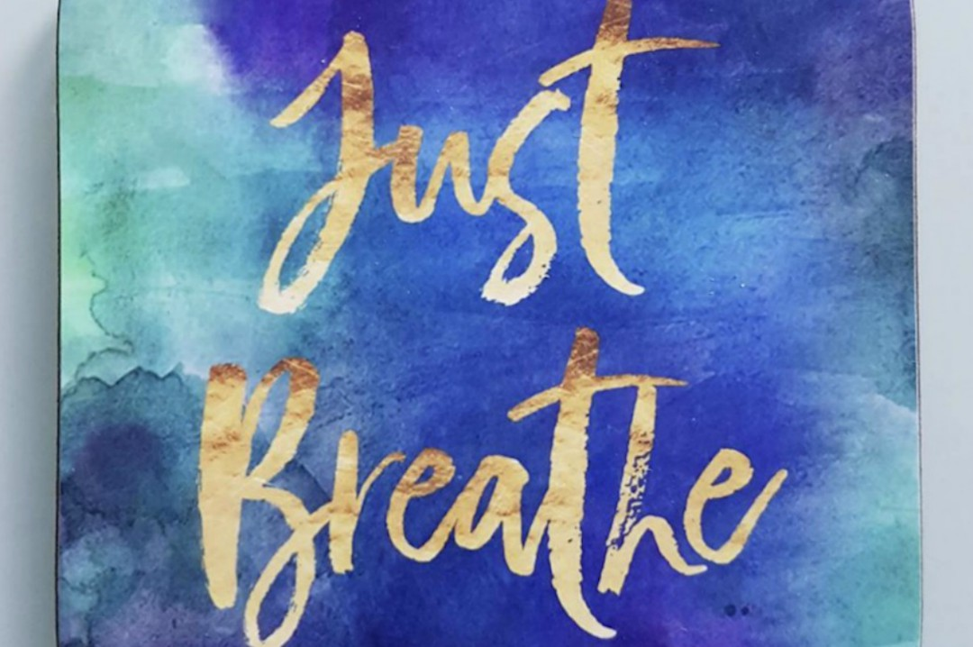 """A photograph of a coaster, with a blue water colour effect on and the words """"just breathe"""" - A Few Hours of Self-Care - A Review of The Space Retreat - Mrs H's favourite things"""