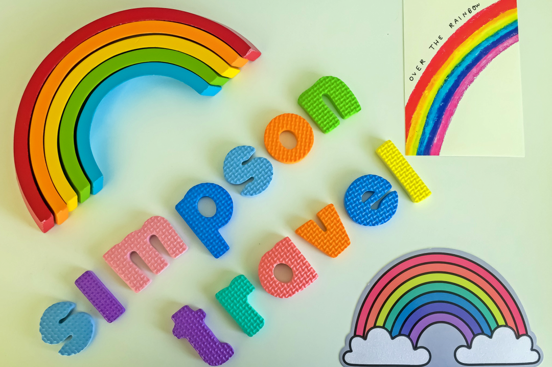 """A photograph of a wooden rainbow toy (showing only the red, orange yellow, green and blue arc of the rainbow), two postcards of rainbows and foam letters spelling out """"Simpson Travel"""" - Chasing Rainbows with Simpson Travel - Mrs H's favourite things"""