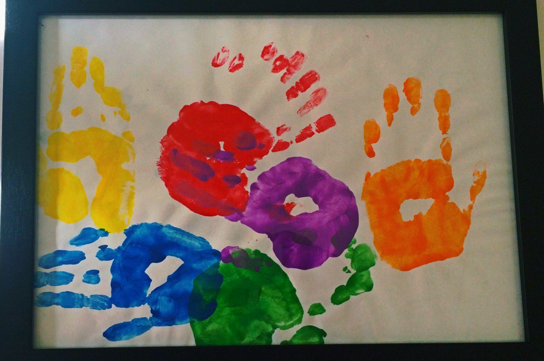 A photograph of a colourful painting of a child's hand prints framed to be a decoration in a child's bedroom - 5 Bedroom Decoration Ideas That Your Child Will Love - Mrs H's favourite things
