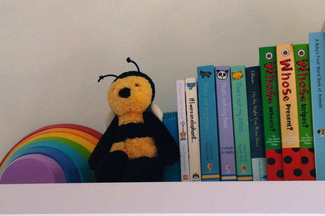 A photograph of a book shelf in a child's bedroom with some colourful books, a bumblebee and a wooden rainbow - 5 Bedroom Decorating Ideas That Your Child Will Love - Mrs H's favourite things