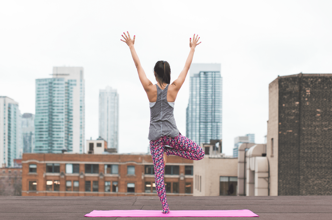 A photograph of a woman doing yoga on a building rooftop - 5 Obstacles To Happiness That You Can Overcome - Mrs H's favourite things