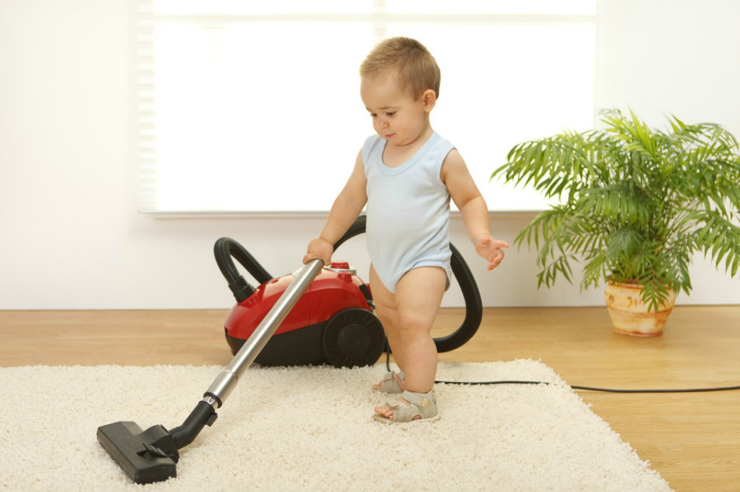 A photograph of a toddler boy vacuuming in his home - 8 Safety Rules For Your Family Home - Mrs H's favourite things