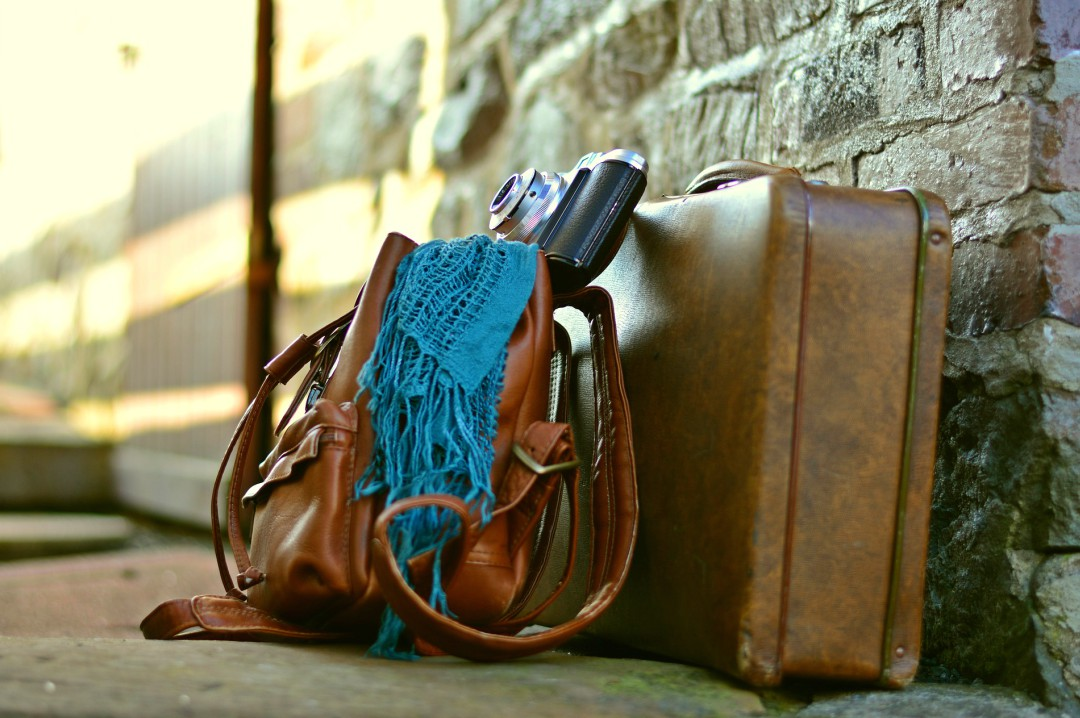 A photograph of a leather bag and suitcase with an old fashioned camera and a petrol blue shawl leaning up against a sand stone brick wall - How To Feel Better Within The Walls of Your Own Home - Mrs H's favourite things