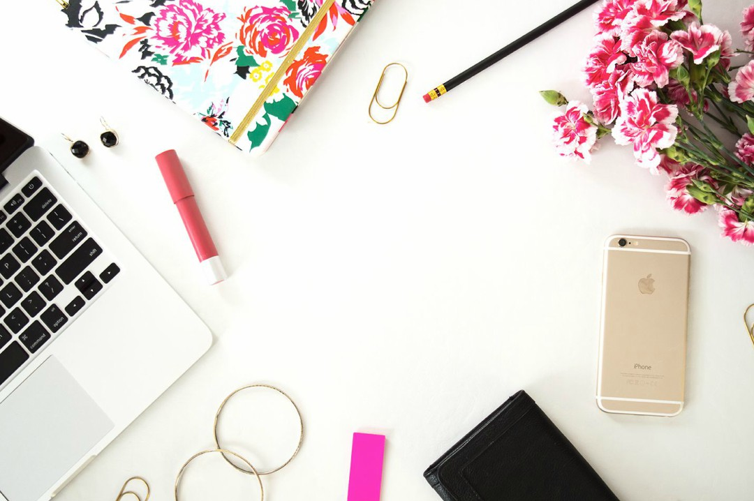 A stock image photograph of a white Mac (just seen) on a white desk, surrounded by a flowery notebook, a red lipstick, some pink carnations, some rose gold paperclips, a pencil, some hoops, some earrings and a rose gold iPhone - How To Turn Blogging Into A Career - Mrs H's favourite things