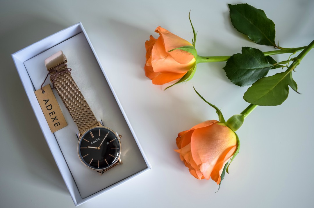 A photograph of the Meek Rosegold Grande watch from Adexe and two orange roses - Mother's Day Gift List - Treats for the Mother's in your Life - Mrs H's favourite things
