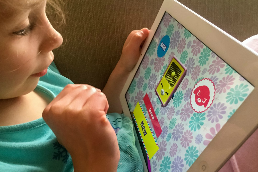 A photograph of a little girl playing the Shopkins Happy Places App created by Kuato Studios and Moose Toys - Shopkins Happy Places App Review - Mrs H's favourite things