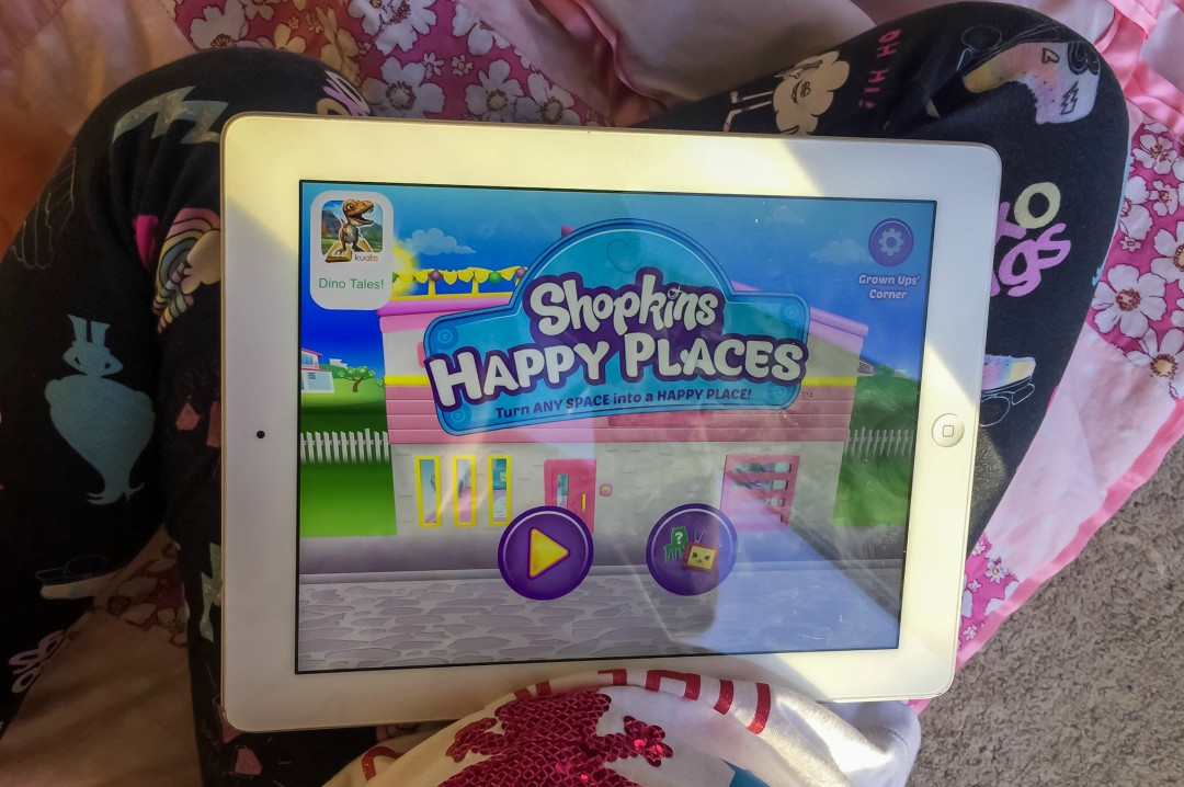 A photograph of a young girl playing the Shopkins Happy Places App from Kuato Studios - Shopkins Happy Places App Review - Mrs H's favourite things