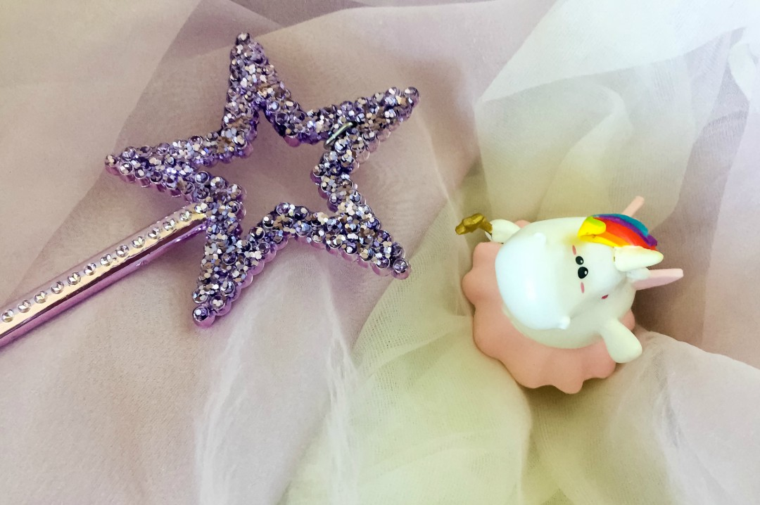 A photograph of a Bullyland Chubby Unicorn Fairy Figure sitting on a purple and cream chiffon dress and a sparkly purple wand - Bullyland Chubby Unicorn Figurines- A Review - Mrs H's favourite things
